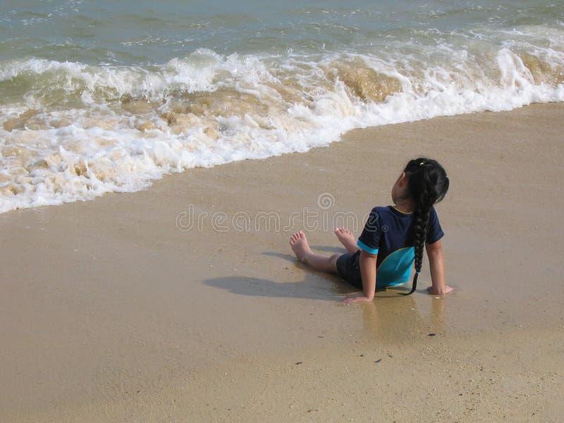 Junges asiatisches Kind, Mädchen, das entlang der Wellen auf Strand anstarrt lizenzfreie stockfotos