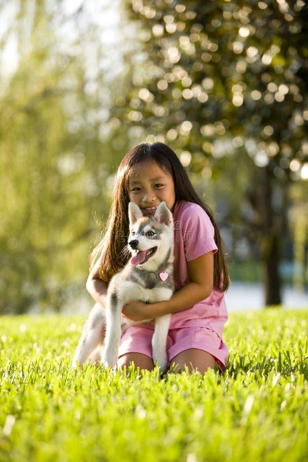 Junges asiatisches Mädchen, das den Welpen sitzt auf Gras umarmt stockbilder