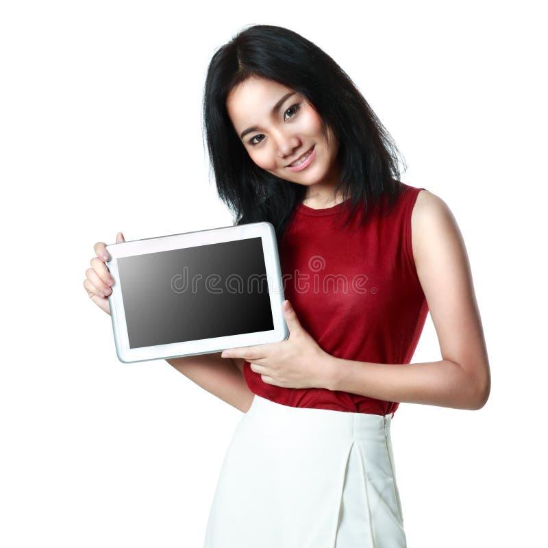 Junges asiatisches Mädchen, das einen Tablet-Computer hält stockbild
