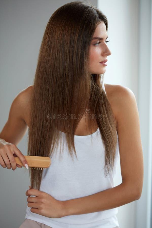 Junges asiatisches Mädchen, das Haar mit dem Finger getrennt auf weißem Hintergrund kämmt Schönes weibliches Haarbürsten langes H stockbild