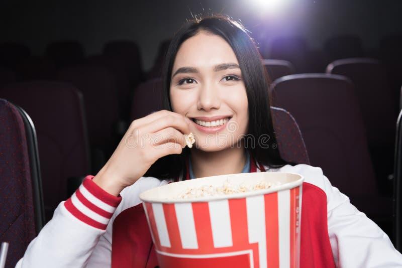 junges asiatisches Mädchen, das Popcorn isst und Film aufpasst stockfotografie