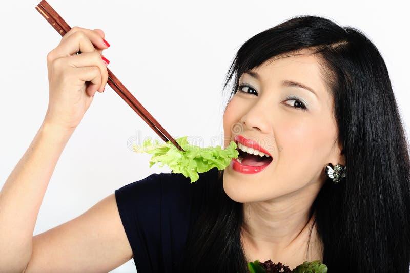 Junges asiatisches Mädchen, das Salat isst lizenzfreie stockfotografie