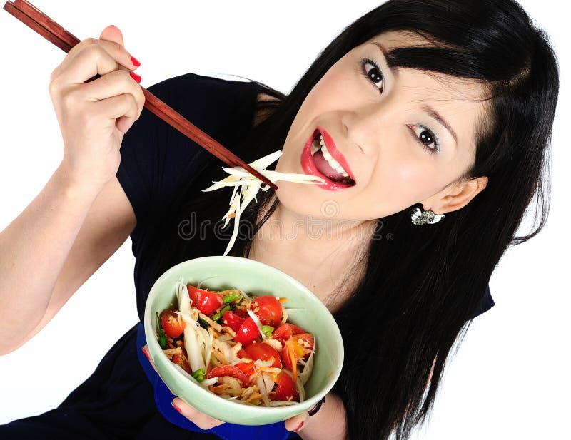 Junges asiatisches Mädchen, das Salat isst lizenzfreie stockfotos