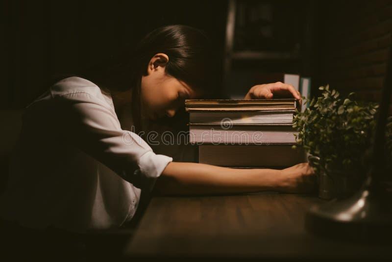 Junges asiatisches Mädchen, das schläft, durch die Studie müde zu sein lizenzfreie stockfotografie
