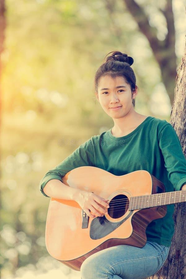 Junges asiatisches Mädchen im Wald, der Gitarre spielt stockfotos