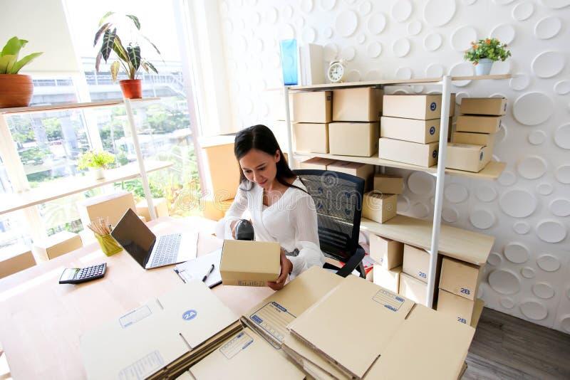 Junges asiatisches Mädchen ist Freiberufler Startung Kleinunternehmerschreibensadresse auf Pappschachtel am Arbeitsplatz und vers lizenzfreie stockfotografie