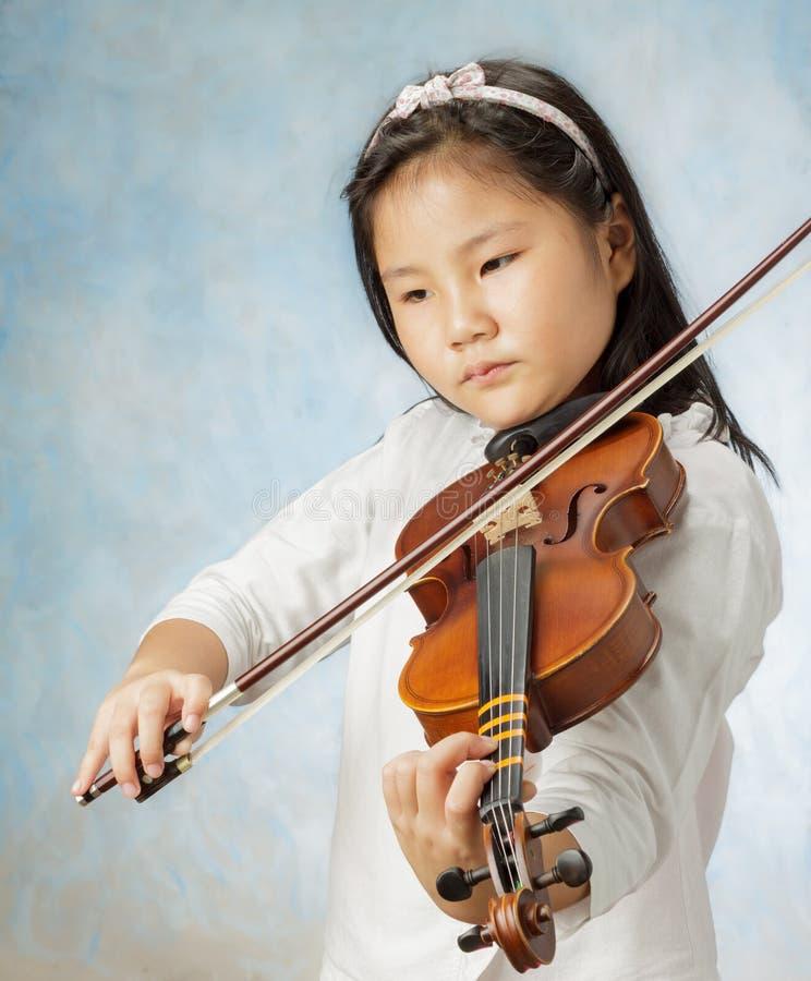 Junges asiatisches Mädchen spielte Violine stockbild