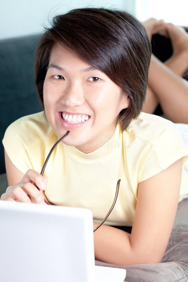 Junges asiatisches Mädchen, welches das Netz auf Couch durchstöbert stockbild