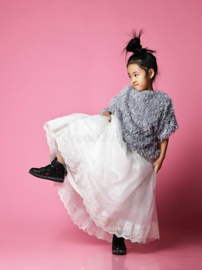 Junges asiatisches Mädchenkind im langen weißen Rock, graue flaumige Strickjacke und schwarze Stiefel treten an kräftig stockfoto