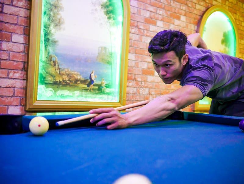 Junges asiatisches Mannspielbillard im bunten Verein - Zielen des weißen Balls zum Schuss lizenzfreie stockfotos