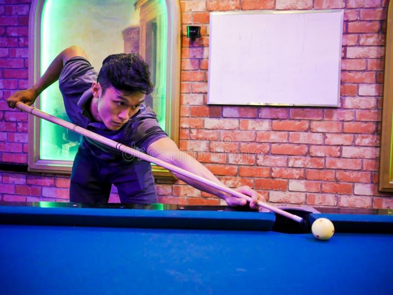 Junges asiatisches Mannspielbillard im bunten Verein - Zielen des weißen Balls zum Schuss lizenzfreies stockfoto