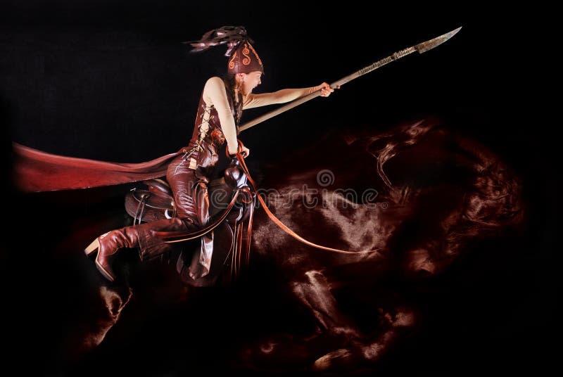 Junges asiatisches Modell in der nationalen Kleidung der Nomaden im Sattel, der im Studio possing ist stockfoto