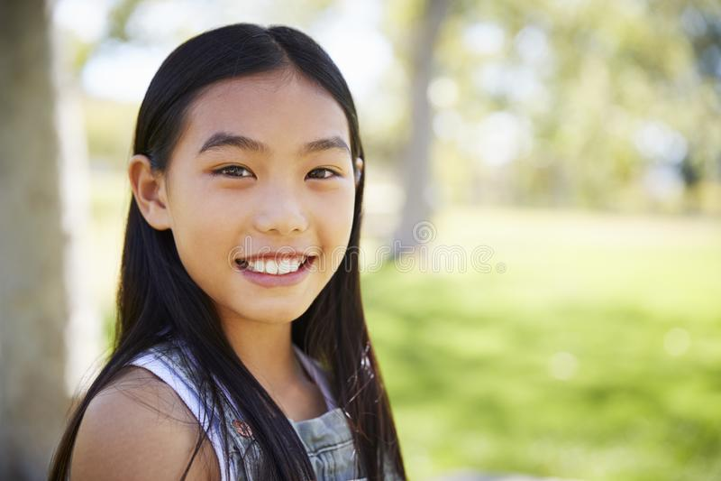 Junges asiatisches Schulmädchen, das oben zur Kamera, Abschluss lächelt lizenzfreie stockfotos