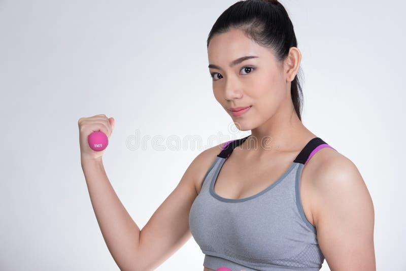 Junges asiatisches Sport- Frauentraining mit Dummkopf Hübsches athlet lizenzfreies stockfoto