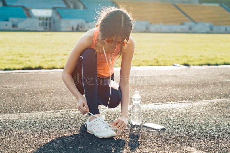 Junges athletisches jugendlich Mädchen, das am Stadion am sonnigen Abend des Frühlinges läuft stockfoto