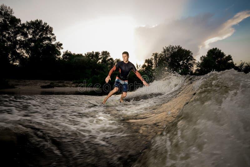 Junges attraktives aktives Mannreiten auf dem wakeboard auf dem See lizenzfreie stockfotos