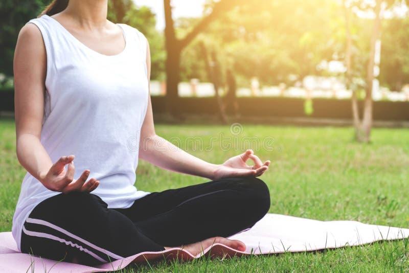 Junges attraktives asiatisches Mädchenpraxisyoga und entspannt sich im Park, stockfoto