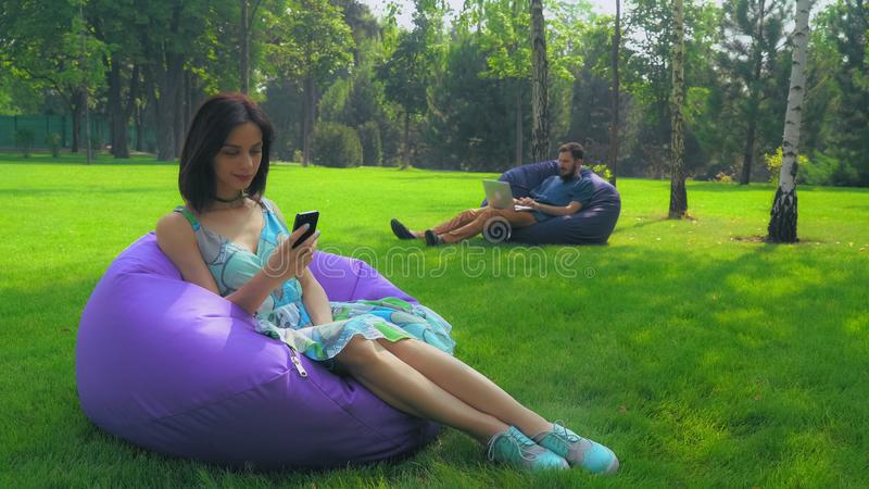Junges attraktives Brunettemädchen sitzt in einem Stuhl im Park und gewinnt eine Mitteilung am Telefon lizenzfreies stockbild