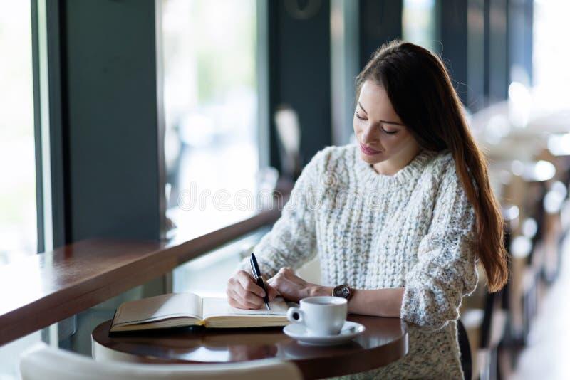 Junges attraktives Frauenschreibenstagebuch im Café lizenzfreie stockfotografie