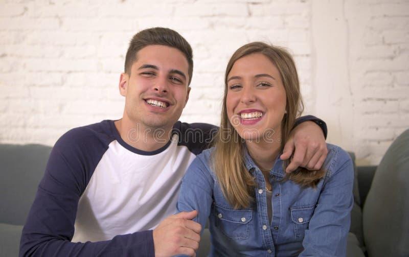 Junges attraktives glückliches und romantisches Couchlächeln des Paarfreund- und -freundinumarmungsangebots zu Hause spielerisch  lizenzfreie stockfotos