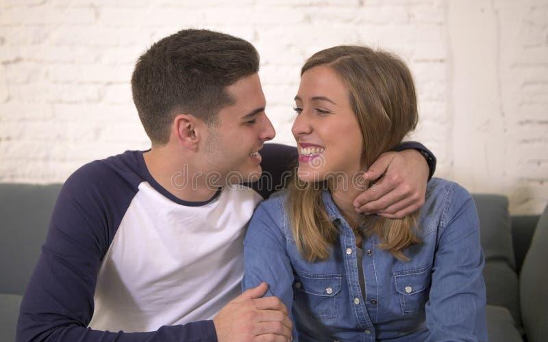 Junges attraktives glückliches und romantisches Couchlächeln des Paarfreund- und -freundinumarmungsangebots zu Hause spielerisch  stockbilder
