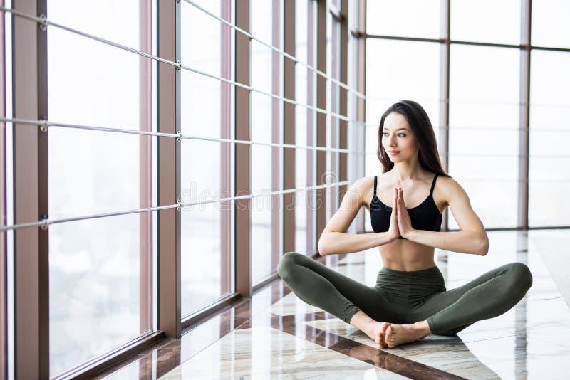 Junges attraktives lächelndes übendes Yoga der Frau, sitzend in halber Lotus-Übung, Haltung Ardha Padmasana lizenzfreie stockbilder