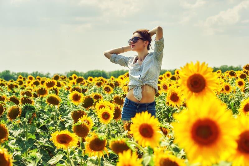 Junges attraktives Mädchen auf dem Gebiet mit Sonnenblumen lizenzfreie stockfotografie