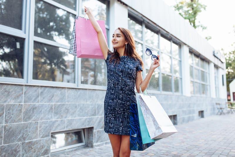 Junges attraktives Mädchen, das gutes in der Stadt, mit Taschen in der Hand kaufen genießt stockfotos