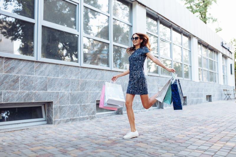 Junges attraktives Mädchen, das gutes in der Stadt, mit Taschen in der Hand kaufen genießt lizenzfreies stockfoto