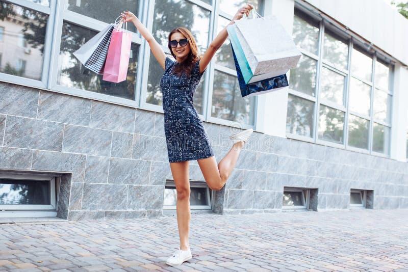 Junges attraktives Mädchen, das gutes in der Stadt, mit Taschen in der Hand kaufen genießt lizenzfreie stockfotografie