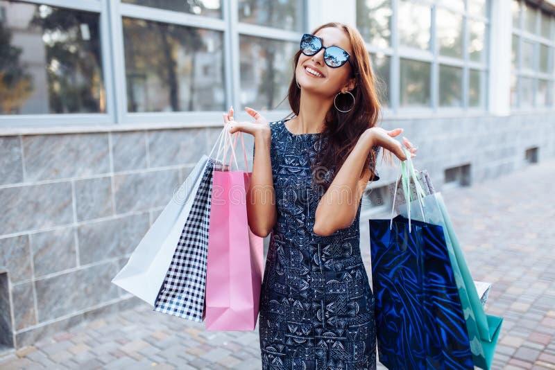 Junges attraktives Mädchen, das gutes in der Stadt, mit Taschen in der Hand kaufen genießt stockfotografie