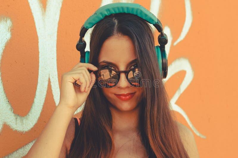 Junges attraktives Mädchen, das Kamera betrachtet, während Musik hört lizenzfreies stockbild