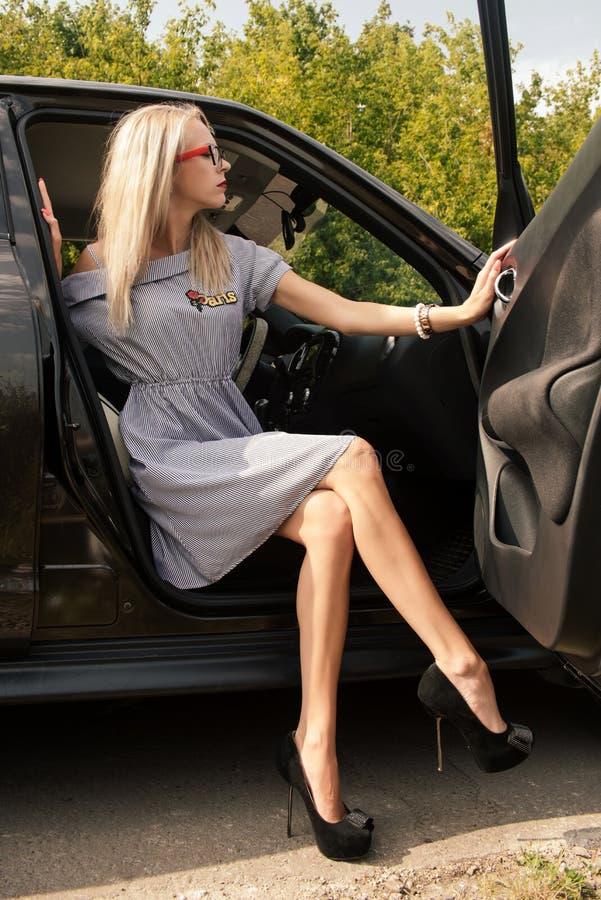 Junges attraktives Mädchen in den Gläsern streifte Kleid und Stöckelschuhe sitzt im Auto, welches die Tür öffnet stockfotos