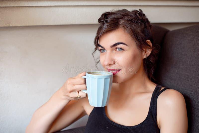 Junges attraktives Mädchen in einem schwarzen T-Shirt und in den Jeans sitzt in einem Café am Tisch und trinkt Kaffee in einer We stockfotos