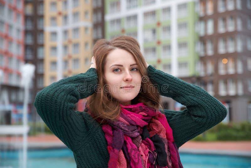 Junges attraktives Mädchen in einer Strickjacke und in einem Schal, Haltungen für ein portra lizenzfreies stockfoto