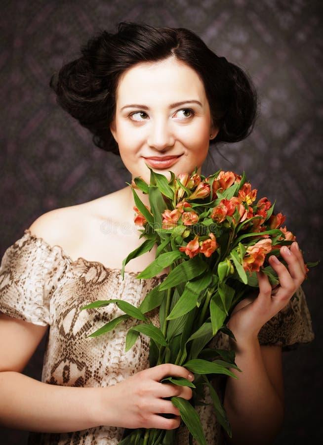 Junges attraktives junges Mädchen hält den Blumenstrauß des Rotes und des Gelbs stockfotografie