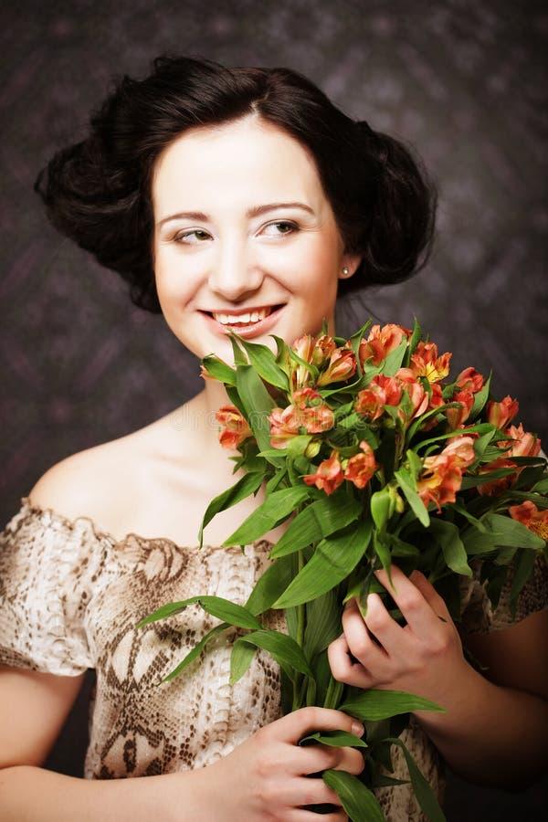 Junges attraktives junges Mädchen hält den Blumenstrauß des Rotes und des Gelbs lizenzfreie stockfotos