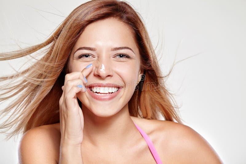 Junges attraktives Mädchen lächelt und reibt seine Nase auf Creme lizenzfreies stockfoto