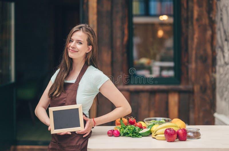 Junges attraktives Mädchen mit einer leeren Platte lizenzfreie stockfotografie