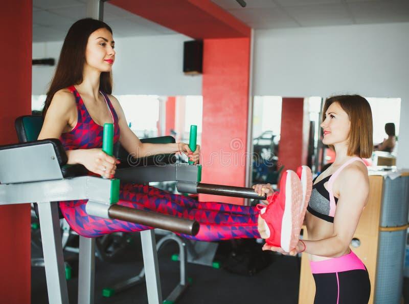 Junges attraktives Mädchen mit persönlichem Trainer in der Turnhalle lizenzfreie stockfotos