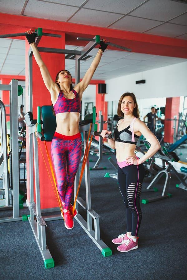 Junges attraktives Mädchen mit persönlichem Trainer in der Turnhalle stockfotos
