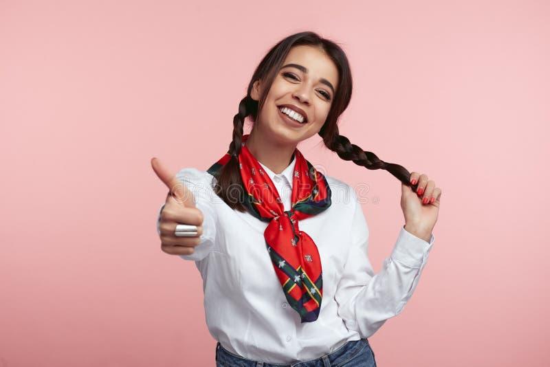 Junges attraktives Mädchen stellt wie die Geste dar, die mit etwas, tragendem weißem Hemd und Schal erfüllt ist und steht übe lizenzfreie stockfotografie