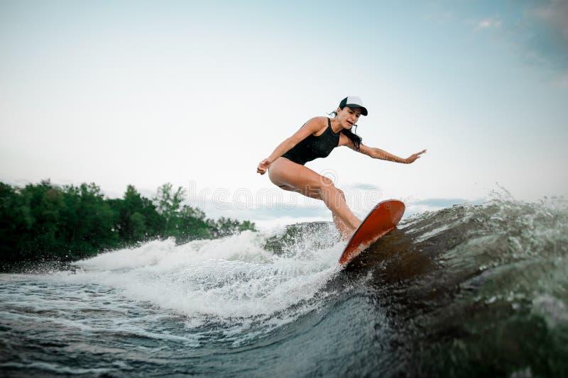 Junges attraktives Mädchenreiten auf dem orange wakesurf lizenzfreies stockbild