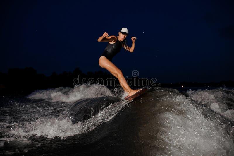 Junges attraktives Mädchenreiten auf dem orange wakesurf in der Nacht stockfoto