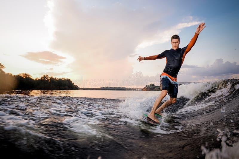 Junges attraktives Mannreiten auf dem grünen wakeboard stockfotos