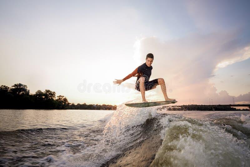Junges attraktives Mannreiten auf dem wakeboard auf dem Hintergrund O lizenzfreies stockfoto