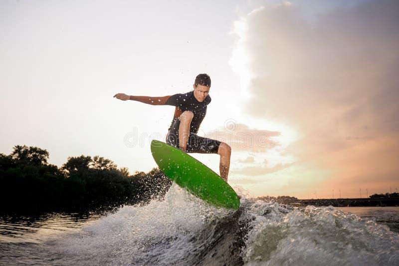 Junges attraktives Mannreiten auf dem wakeboard auf dem Hintergrund O stockfotos