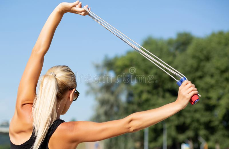 Junges attraktives Modell mit dem perfekten dünnen Körper, der das Ausdehnen mit Seilspringen tut lizenzfreies stockbild