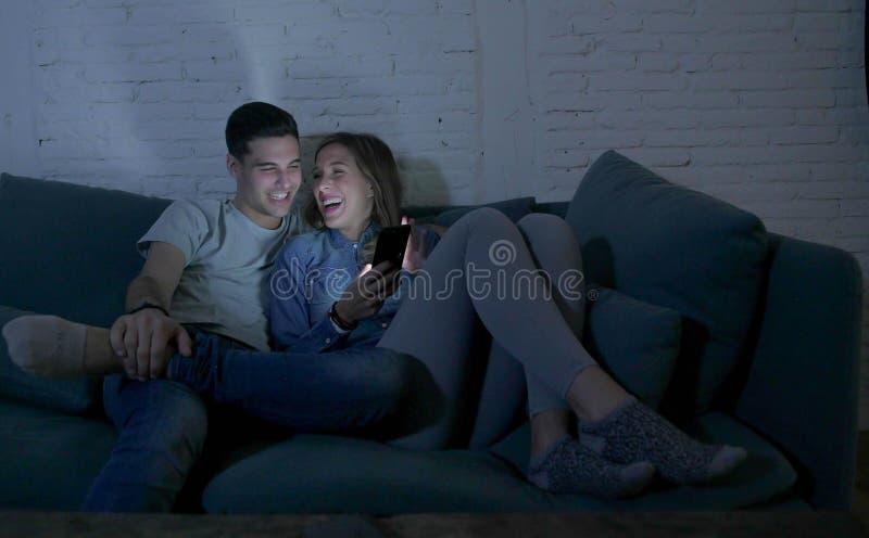 Junges attraktives und glückliches Paar, das Internet-APP am Handy genießt und lacht Wohnzimmer verwendet zusammen, zu Hause sitz stockbilder
