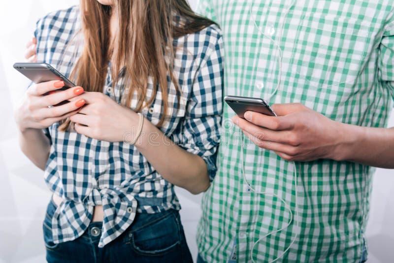 Junges attraktives und glückliches Paar, das Internet-APP am Handy zusammen genießt und lacht verwendet stockfotografie